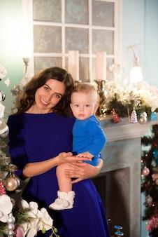 Netter junge und seine mutter, die weihnachtsbaum für feiertag verziert