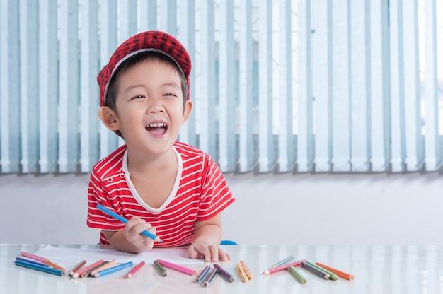 Netter junge zeichnet mit farbstiften im kinderzimmer