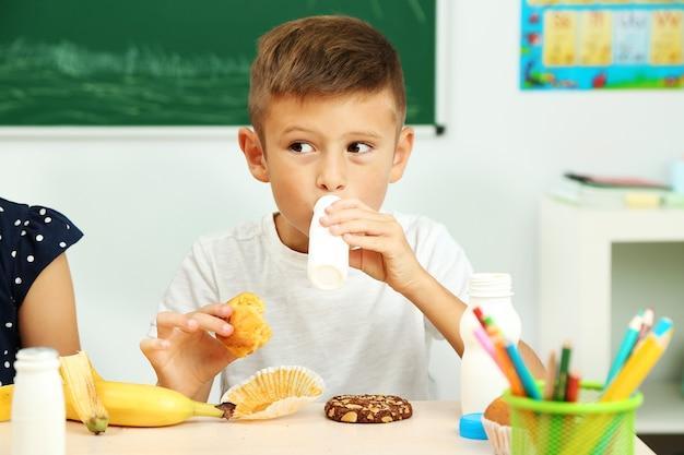 Netter junge zur mittagszeit im klassenzimmer