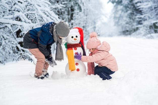 Netter jungen und mädchen, die schneemann im weißen winterwald bauen