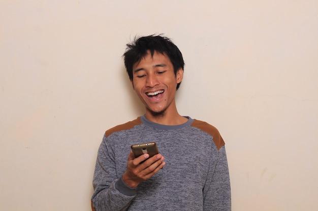 Netter junger asiatischer mann überrascht, lächeln, nachdem er sein smartphone geschaut hat. isoliert mit warmen bac
