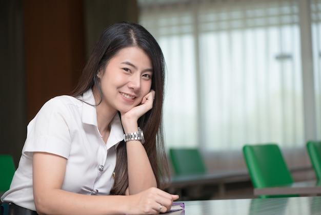 Netter junger asiatischer student im einheitlichen lächeln und sitzen im klassenzimmer, in der ausbildung und im lernen des konzeptes