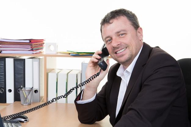 Netter junger erfolgreicher mann spricht am telefon an der tragenden anzugsabnutzung des büroarbeitsplatzschreibtischs
