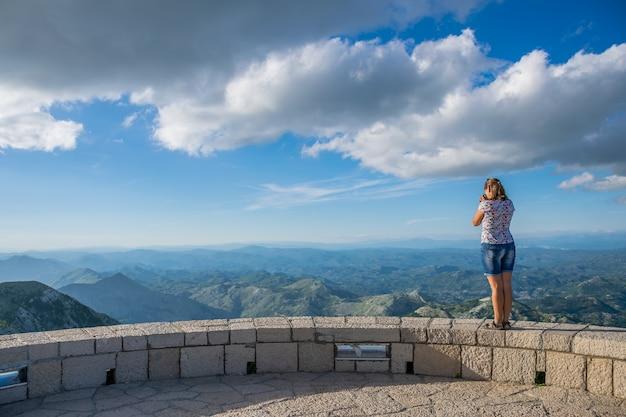 Netter junger fotograf, der landschaft vom standpunkt bewundert