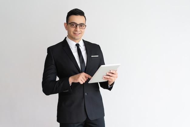 Netter junger geschäftsmann, der e-mail auf tablette überprüft und kamera betrachtet.
