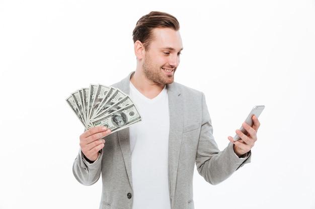 Netter junger hübscher geschäftsmann, der geld hält und handy verwendet.