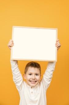 Netter junger lächelnder vorschulkindjunge, der leeres weißes leeres zeichen mit kopienraum lokalisiert hält.