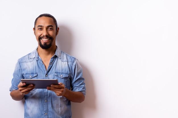 Netter junger latino mann mit barthaar mit großer haltung und lächeln auf seinem gesicht gebunden sieht und hält eine tablette in seinen händen, trägt ein hellblaues hemd mit hochgekrempelten ärmeln und lässt ein leerzeichen