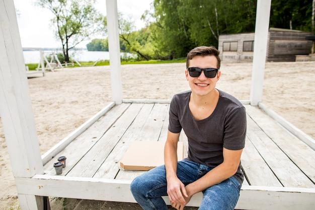 Netter junger mann, der auf strand sitzt