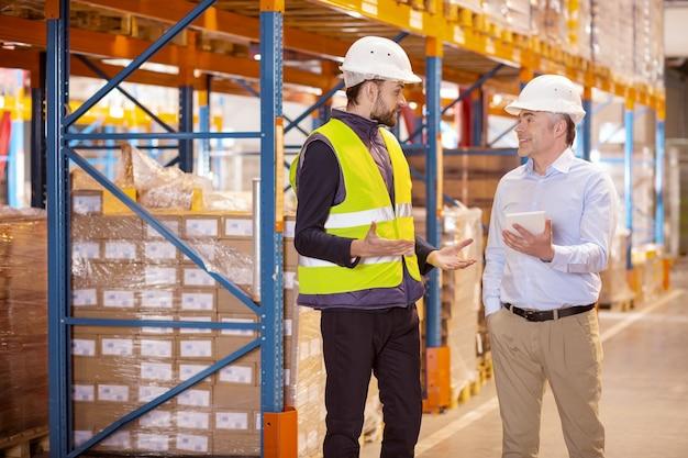 Netter junger mann, der mit dem logistikmanager spricht, während er im lager arbeitet