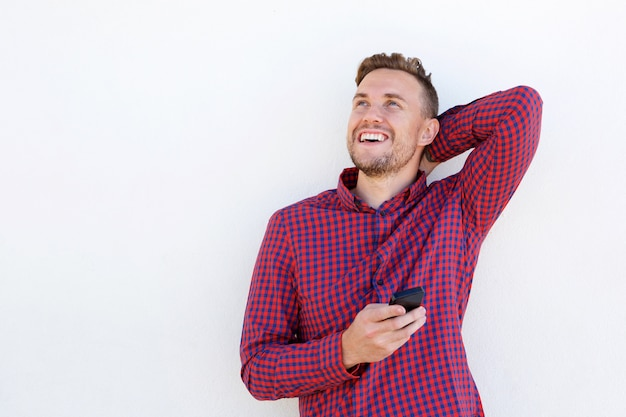 Netter junger mann, der mit handy lacht