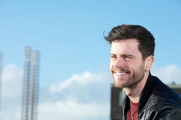 Netter junger mann mit bart draußen lächelnd