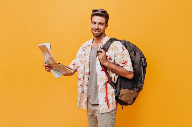 Netter junger mann mit bart und stilvoller frisur in sonnenbrille und weißem hemd, der rucksack und karte hält und auf oranger wand lächelt