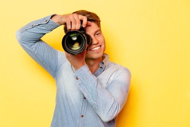 Netter junger mann mit der berufskamera, ein foto machend. auf gelbem hintergrund.