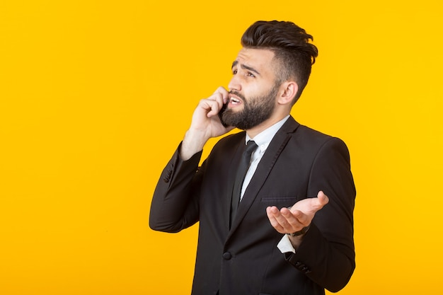 Netter junger mann mit einem bart in der formellen kleidung, die am telefon spricht, das auf einer gelben wand aufwirft