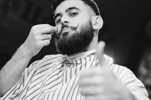 Netter junger mann mit schönem schnurrbart und bart, die in einem sessel im friseursalon sitzen