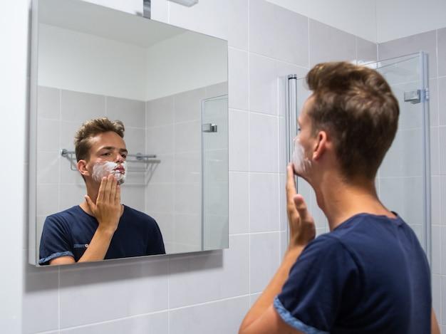 Netter junger mann, teenager rasiert sich zum ersten mal