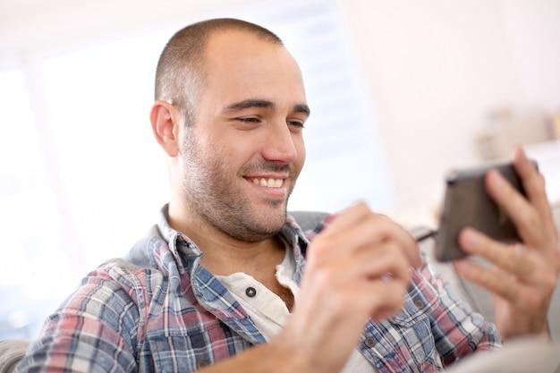 Netter junger mann zu hause unter verwendung des smartphone