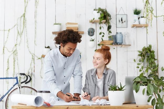 Netter junger rothaariger weiblicher auszubildender, der lächelt, während er dem erfahrenen selbstbewussten architekten zuhört