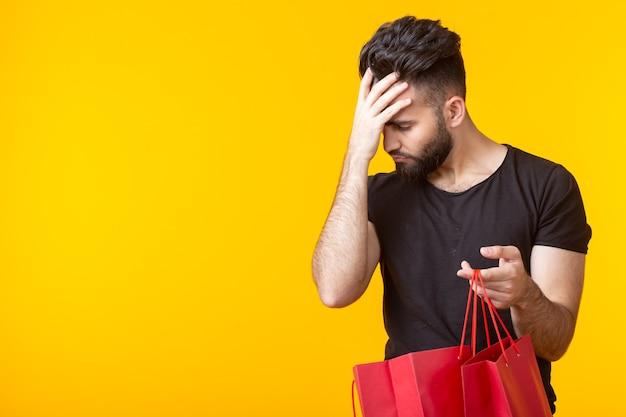 Netter junger trauriger bärtiger mann betrachtet den kauf in einkaufstüten auf einer gelben wand mit kopienraum