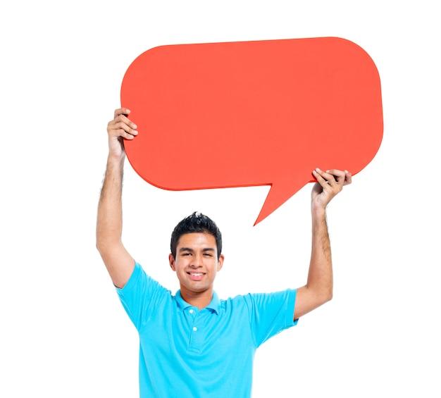 Netter junger zufälliger mann, der spracheblase hält