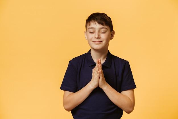 Netter kaukasischer junge gekleidet in lässigem dunkelblauem t-shirt, das gegen gelbe wand in betender haltung mit geschlossenen augen steht. weihnachtswünsche.
