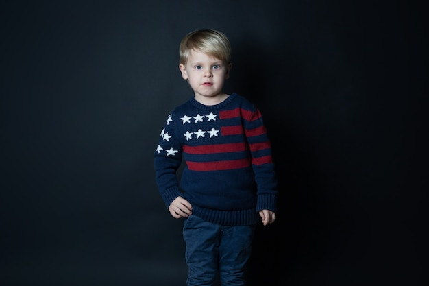 Netter kaukasischer junge im pullover mit amerikanischer flagge der usa auf schwarzem hintergrund