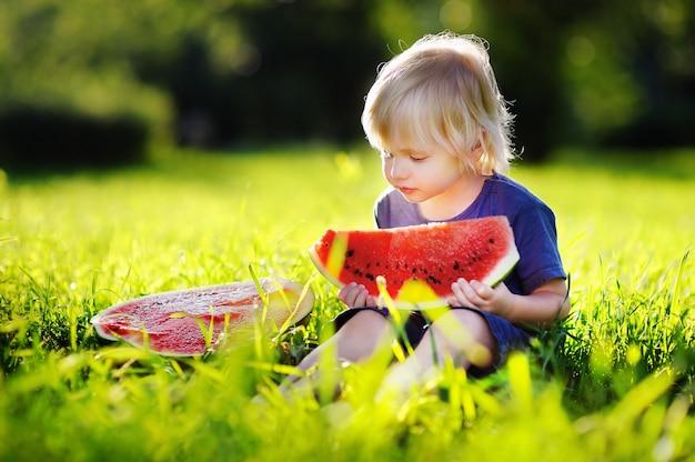 Netter kaukasischer kleiner junge mit den blonden haaren frische wassermelone draußen essend