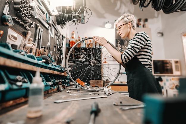 Netter kaukasischer weiblicher arbeiter, der fahrradrad hält und repariert, während er in fahrradwerkstatt steht.