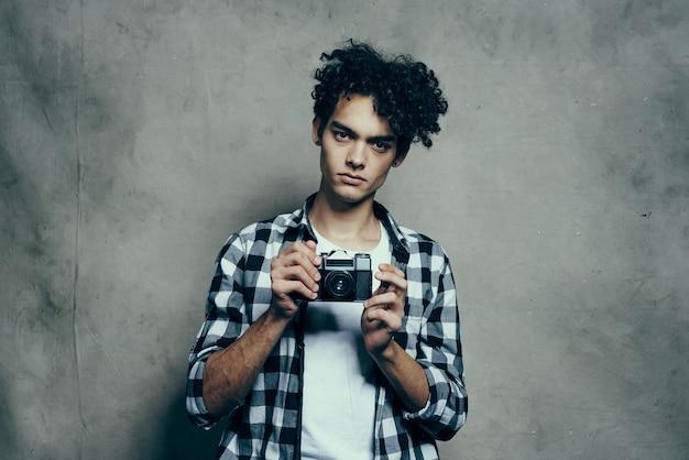 Netter kerl in einem karierten hemd und einem t-shirt mit einer kamera in seinem handmodell-hobbystudio