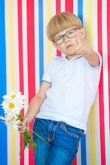Netter kinderabschluß herauf porträt auf buntem. entzückender kleiner junge, der nahe zur wand steht. kind hält einen blumenstrauß.