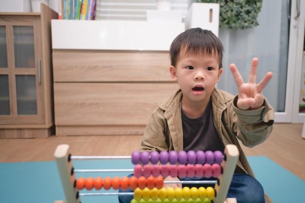 Netter kindergartenjunge, der auf boden mit dem abakus sitzt