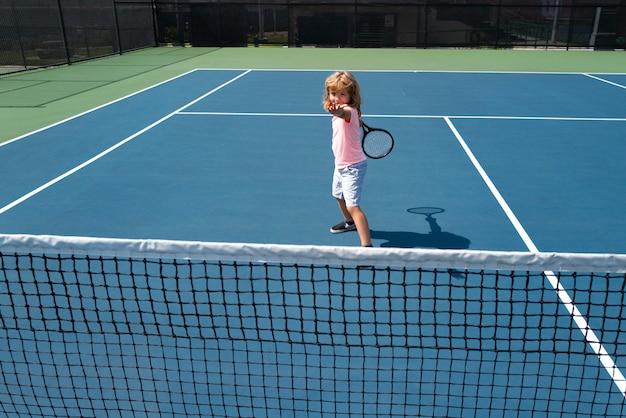 Netter kinderjunge beim tenniswettbewerb. kleiner junge, der tennis am hof spielt.
