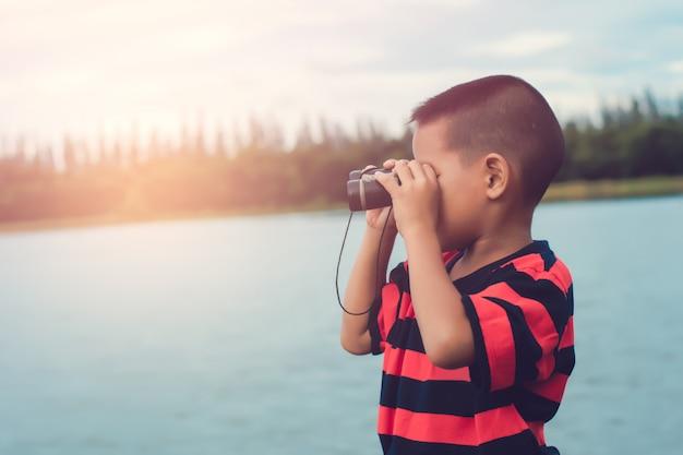 Netter kinderjunge, der auf flussufer steht und im fernglas schaut.