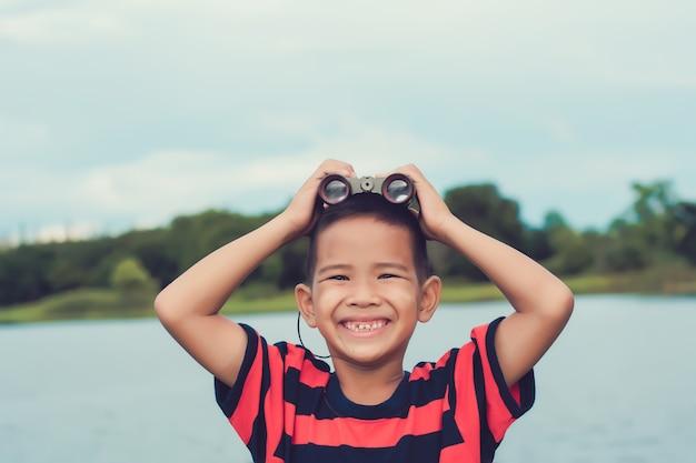 Netter kinderjunge, der auf flussufer und mit fernglas steht. in einer glücklichen stimmung.