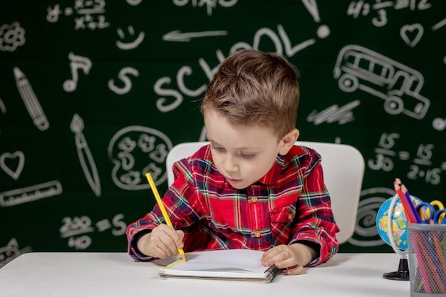 Netter kinderjunge, der hausaufgaben macht. cleveres kind, das am schreibtisch zeichnet. schüler. grundschüler zeichnen am arbeitsplatz. kind lernt gerne. heimunterricht. zurück zur schule. kleiner junge im schulunterricht