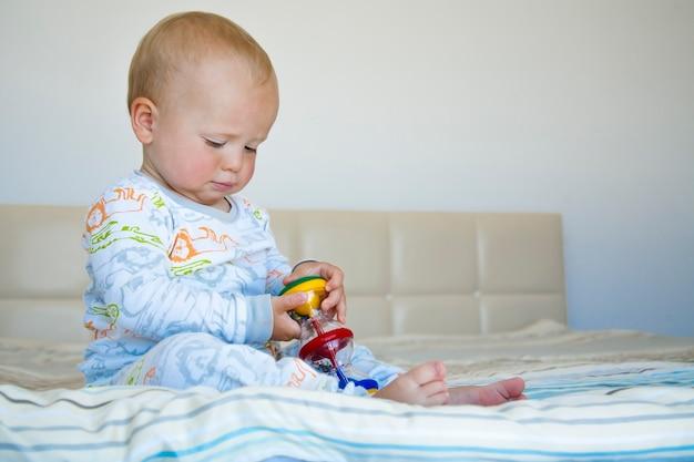 Netter kinderjunge, der im schlafanzug auf dem bett sitzt und mit farbigem spielzeug spielt.