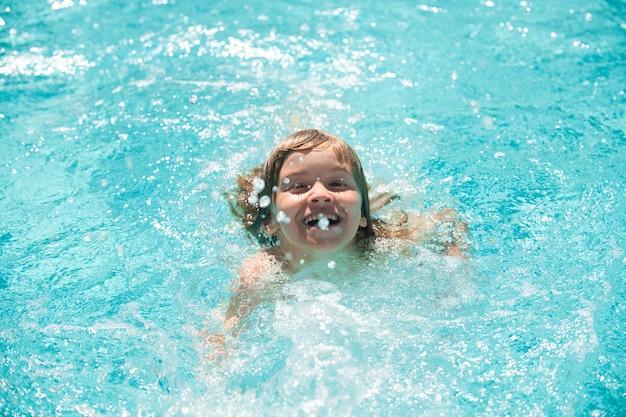 Netter kinderjunge schwimmt im swimmingpool, sommerwasserhintergrund mit kopienraum. lustiges kindergesicht. kleiner junge, der im sommerurlaub im freibad im wasser spielt. kinderschwimmen im außenpool.