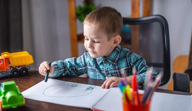 Netter kinderjunge zeichnet mit kreide auf papier in einem album am tisch