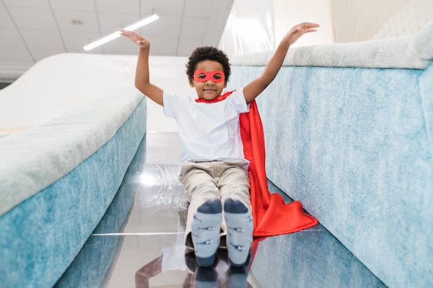 Netter kleiner afrikanischer junge im kostüm des superman, der rutschenrutsche vor kamera auf spielbereich des kinderzentrums nach unten bewegt