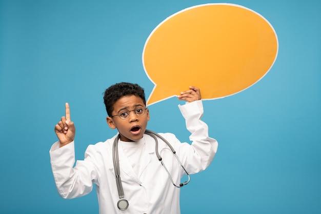 Netter kleiner afrikanischer oder mischlingsarzt in brille und weißmantel, die leere gelbe papier-sprechblase halten