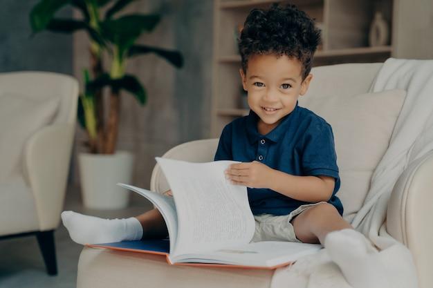 Netter kleiner afroamerikanischer junge, der im sessel mit geschichtenbuch sitzt