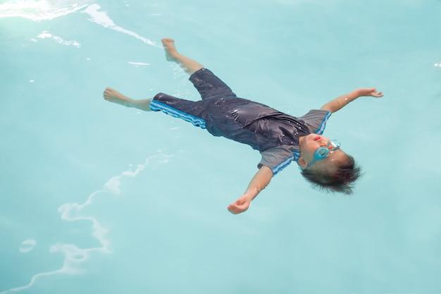 Netter kleiner asiat 30 monate / 2 jahre alte kleinkindbaby lernen, im schwimmenunterricht in thailand zu schwimmen