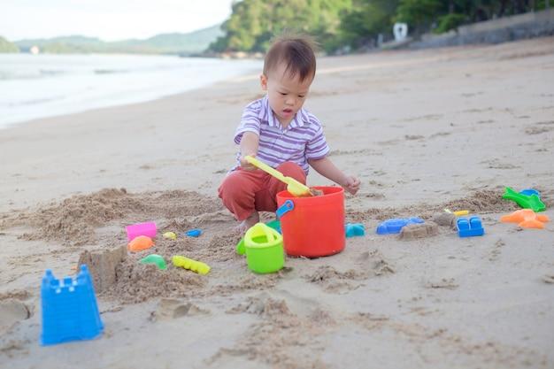Netter kleiner asiatischer 2 jahre alter kleinkindjunge, der kinderstrandspielzeug am schönen tropischen sandstrand sitzt und spielt