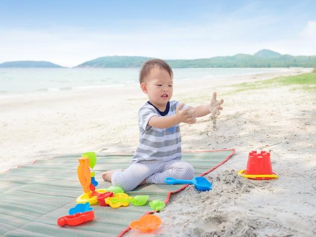 Netter kleiner asiatischer 2 jahre alter kleinkindjunge, der kinderstrandspielzeug auf tropischem sandstrand sitzt und spielt, familienreise, wasser im freien aktivität am strandurlaub, sensorisches spiel mit sandkonzept