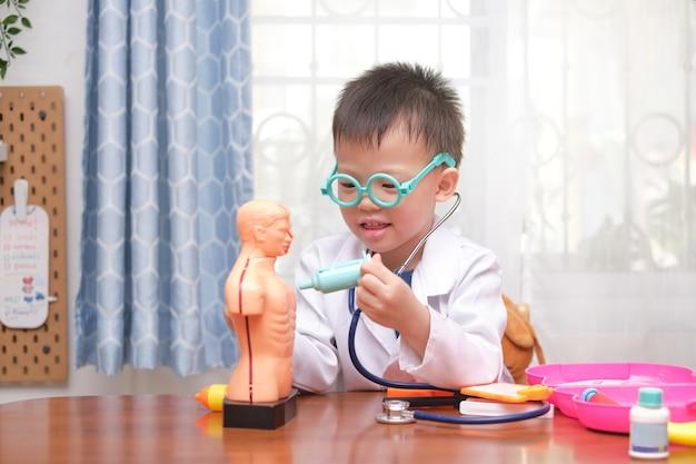 Netter kleiner asiatischer 4-jähriger schuljunge in der arztuniform, der arzt zu hause spielt, kind, das stethoskop lernt und mit anatomischem körperorganmodell spielt