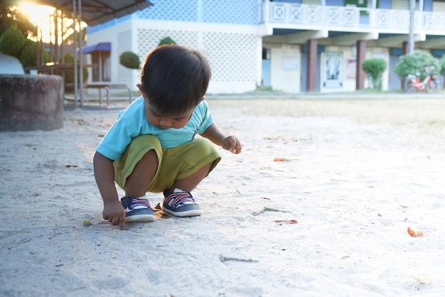 Netter kleiner asiatischer junge, der sand am park spielt