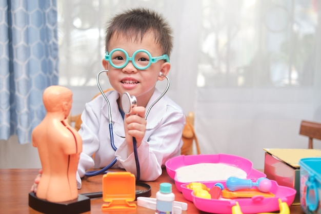 Netter kleiner asiatischer junge in der arztuniform, die doktor zu hause spielt, kind, das stethoskop lernend lernt und mit anatomischem körperorganmodell spielt