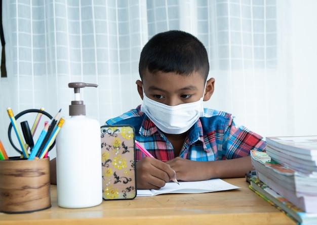 Netter kleiner asiatischer junge online lernen mit smartphone zu hause, coronavirus