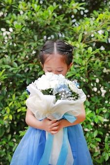 Netter kleiner asiatischer kindermädchen-riechender blumenstrauß von blumen im garten.